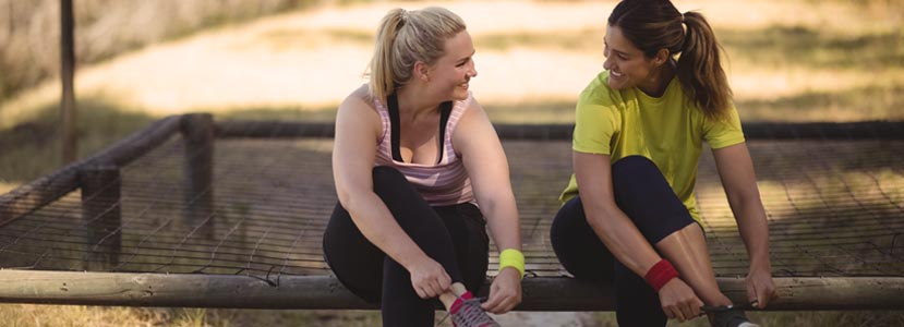 two women talking while tying running shoes