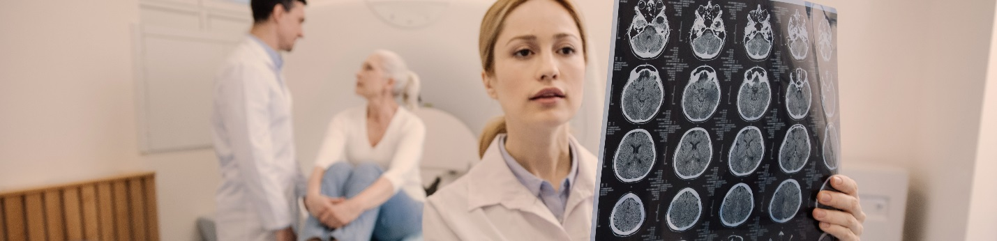 Doctor looking at brain scan with patients in the background