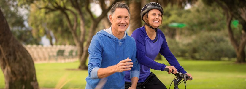 Older couple, husband running and wife riding bike in park